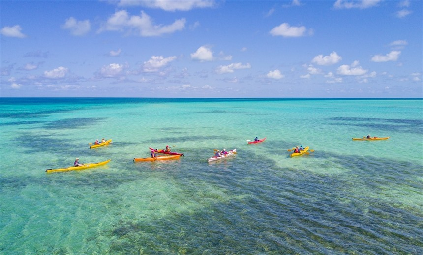 Kayakers navigate the crystal clear waters at Glover's Reef Atoll. © Shutterstock/Duarte Dellarole
